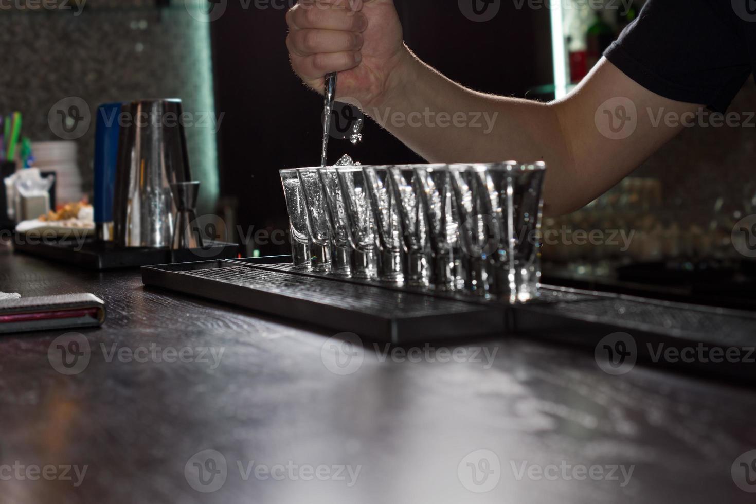 barman vertiendo licor en vasos de chupito foto