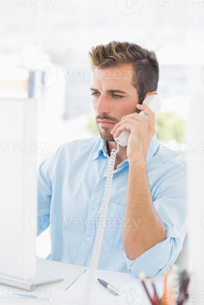 Serious man using phone and computer in office photo