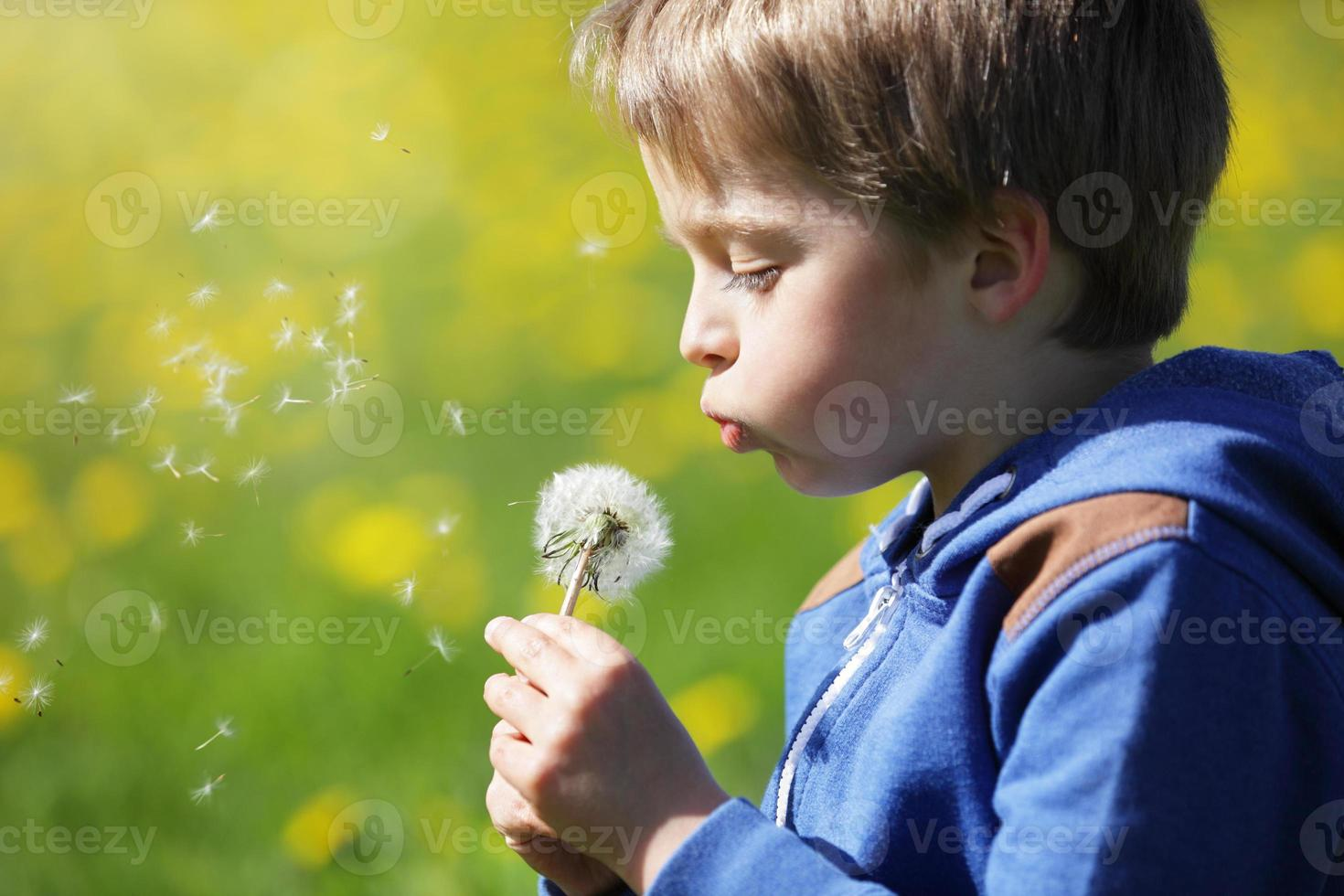 Niño soplando semillas de diente de león en un campo foto