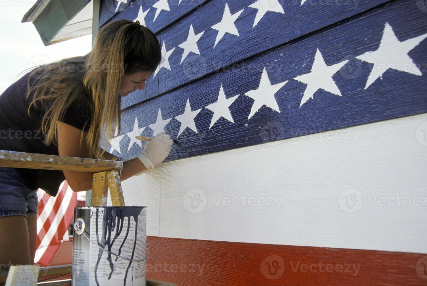 Young woman painting the USA flag on the wall photo