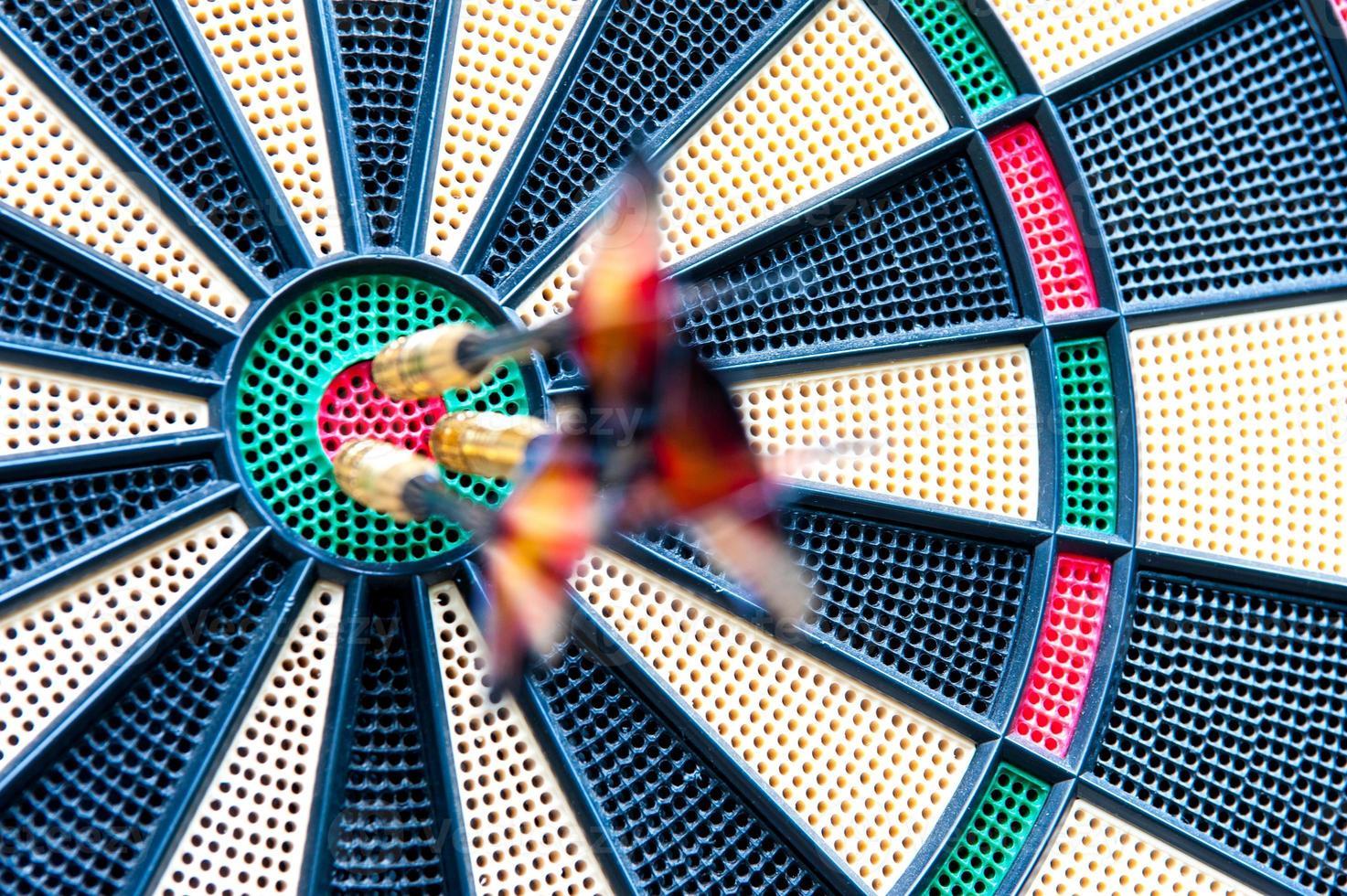 Blurred darts stuck in bulls-eye photo