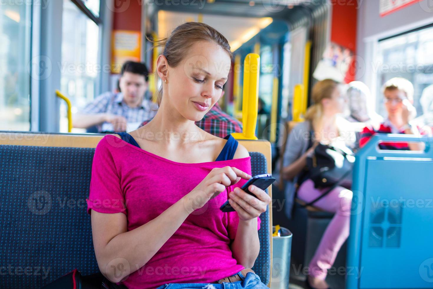 Young woman using a smartphone on a tram photo