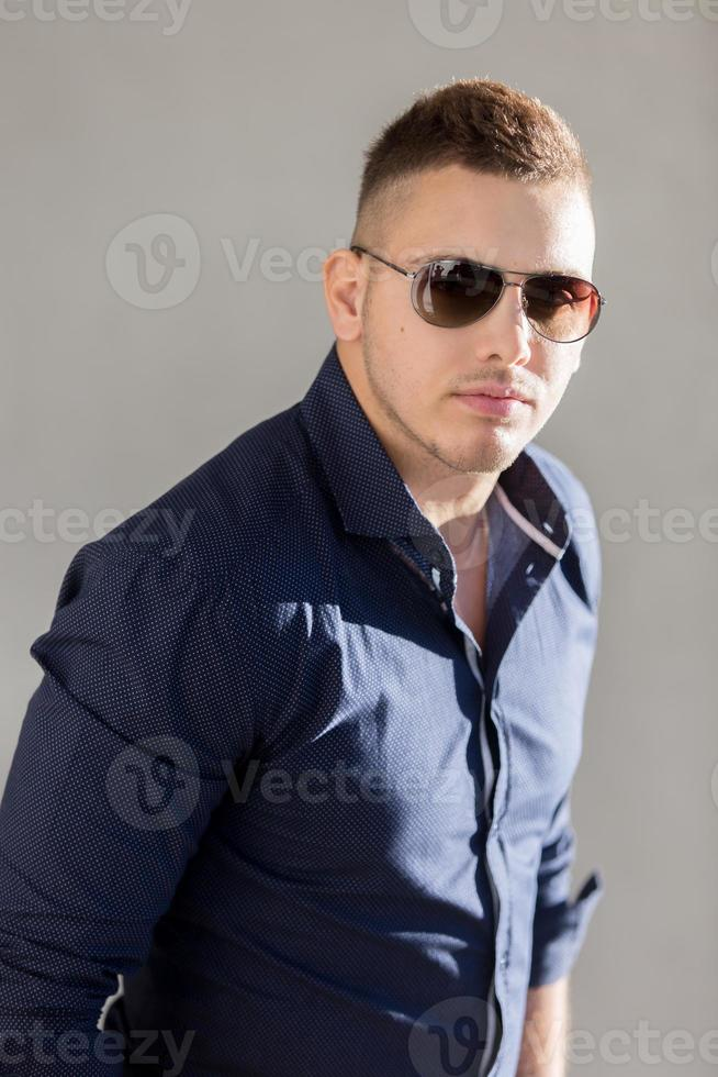 Portrait of good looking guy in sunglasses photo