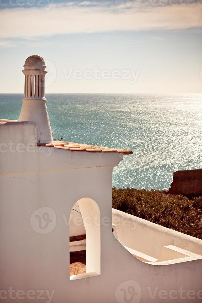 White house on a cliff overlooking the ocean in Portugal photo