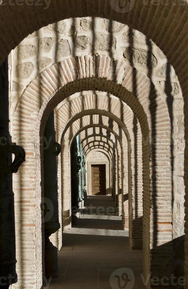 an arched corridor walkway past the front entrances photo