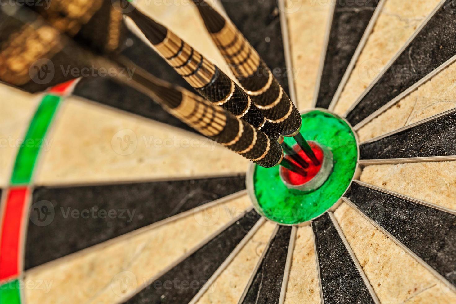 Three darts in bull's eye close up photo