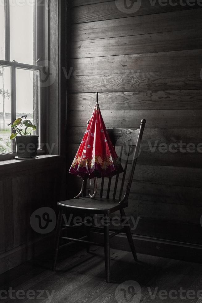 Imagen sepia con paraguas rojo sentado en una silla junto a la ventana foto