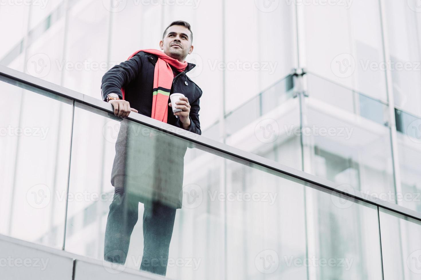 Content dreamy young man with coffee cup looking into distance photo