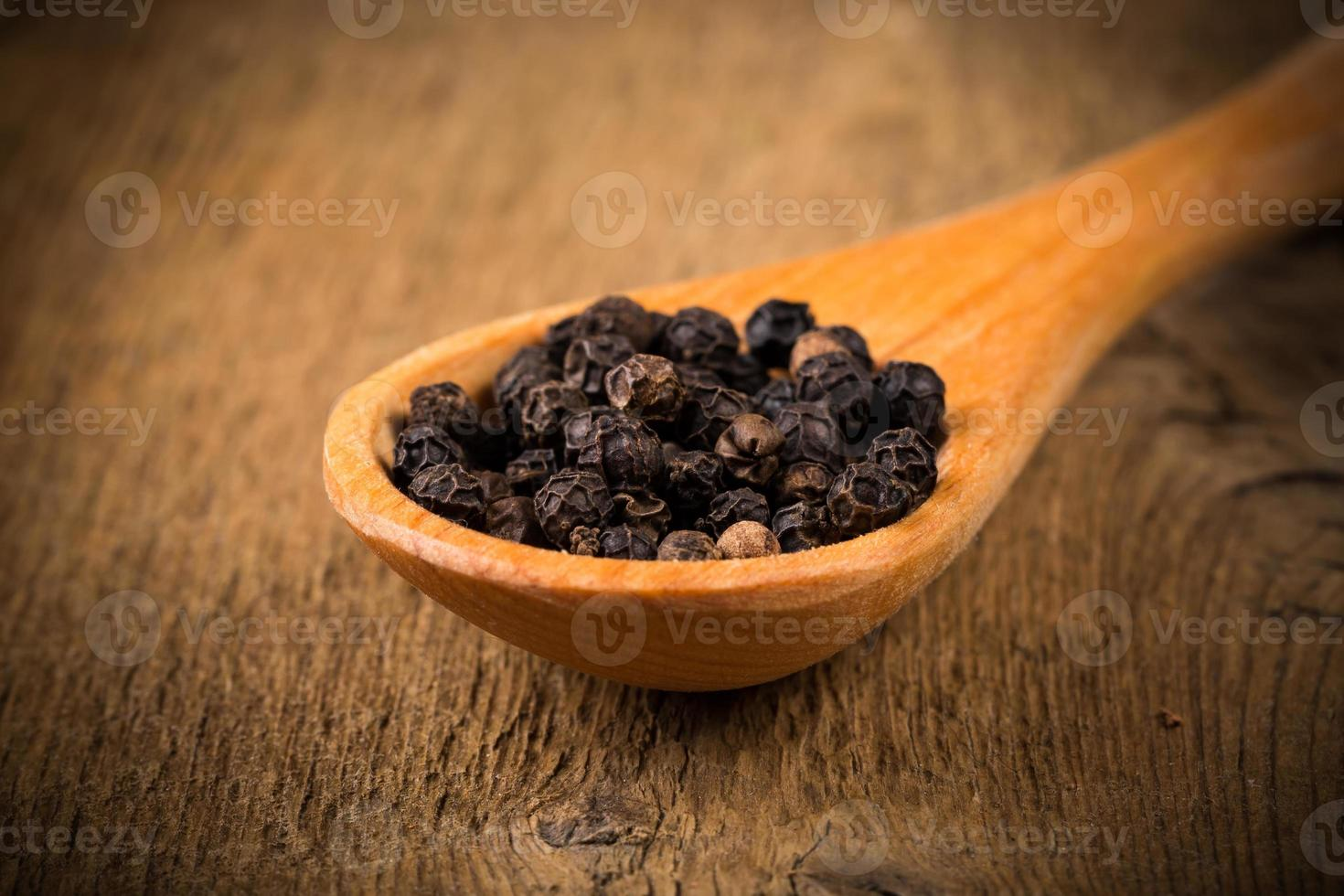 black pepper on wooden spoon photo
