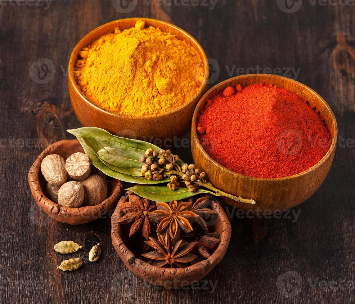 Colorful spices in bowls on wooden background. photo