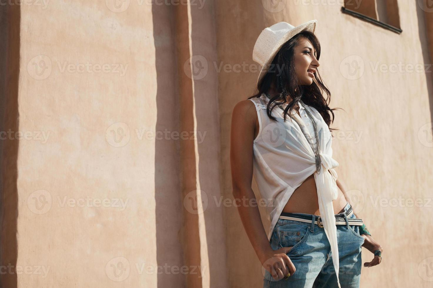 smiling indian lady in casual summer outfit against ancient building photo