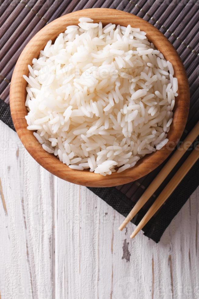 rice in a wooden bowl and chopsticks vertical top view photo