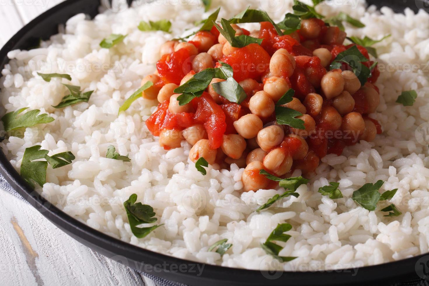 Rice with chickpeas, tomatoes and herbs close-up. Horizontal photo