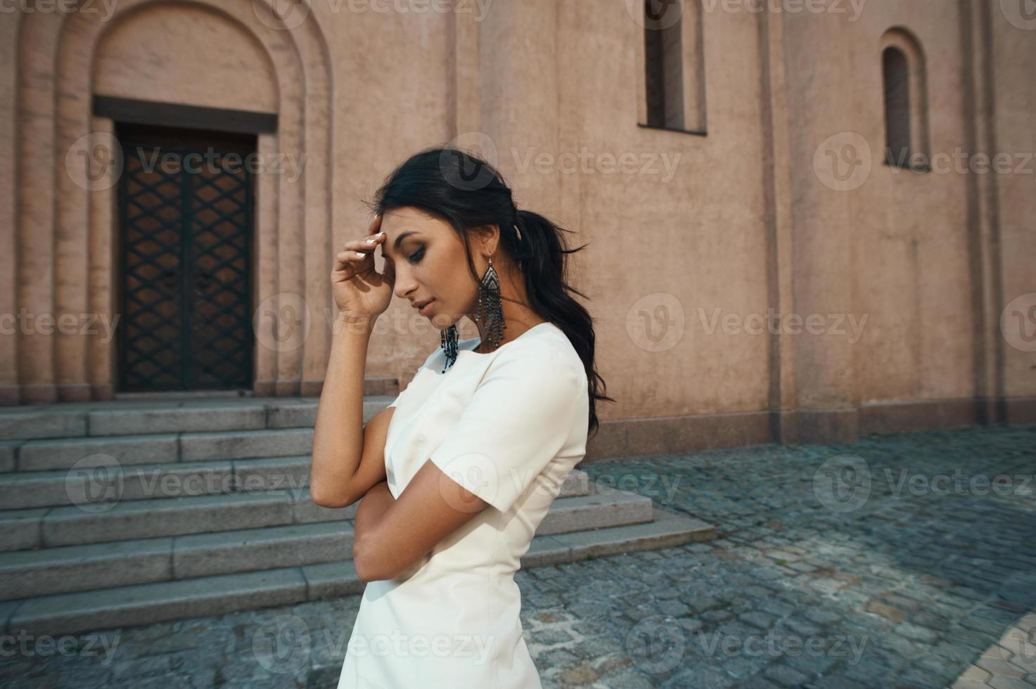 lady in dress against ancient building with thoughtful look photo