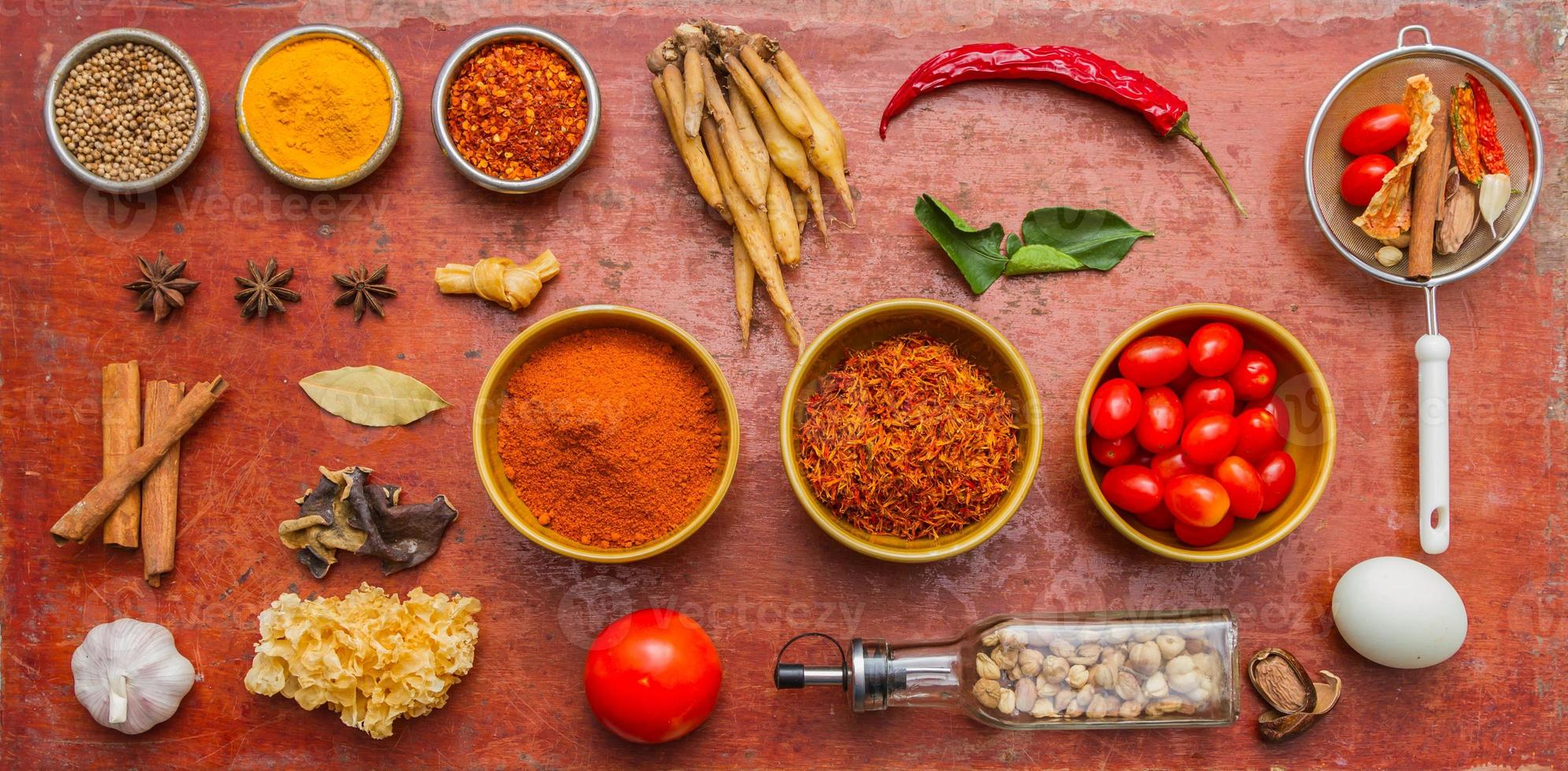 Mixed spices and herbs on red background. photo