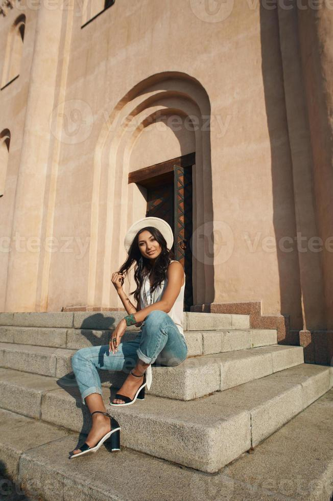 flirting indian lady in casual summer outfit against ancient building. photo