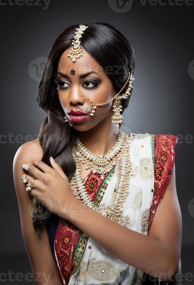 mujer india en vestimentas tradicionales con maquillaje de novia y joyas foto