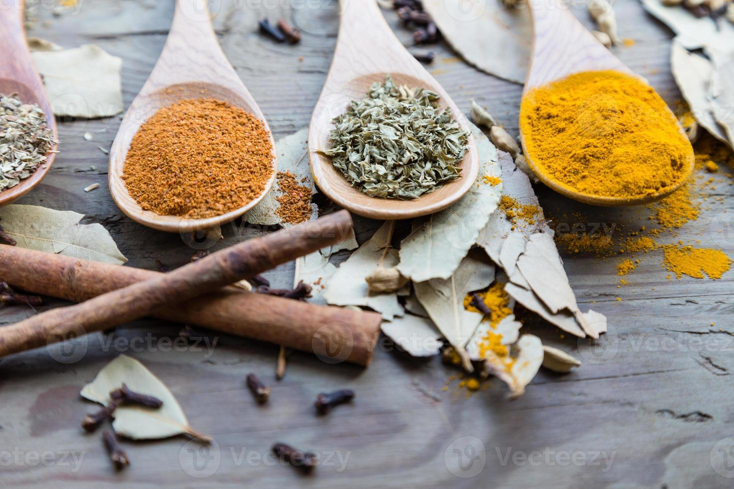 Spices in spoons on wooden table photo