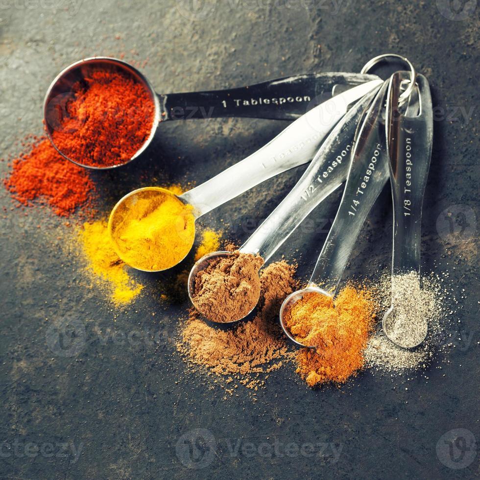 especias coloridas en cucharas de metal foto