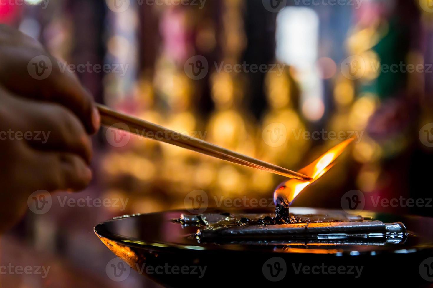lámpara de aceite grande con la mano toma un joss stick encendido foto