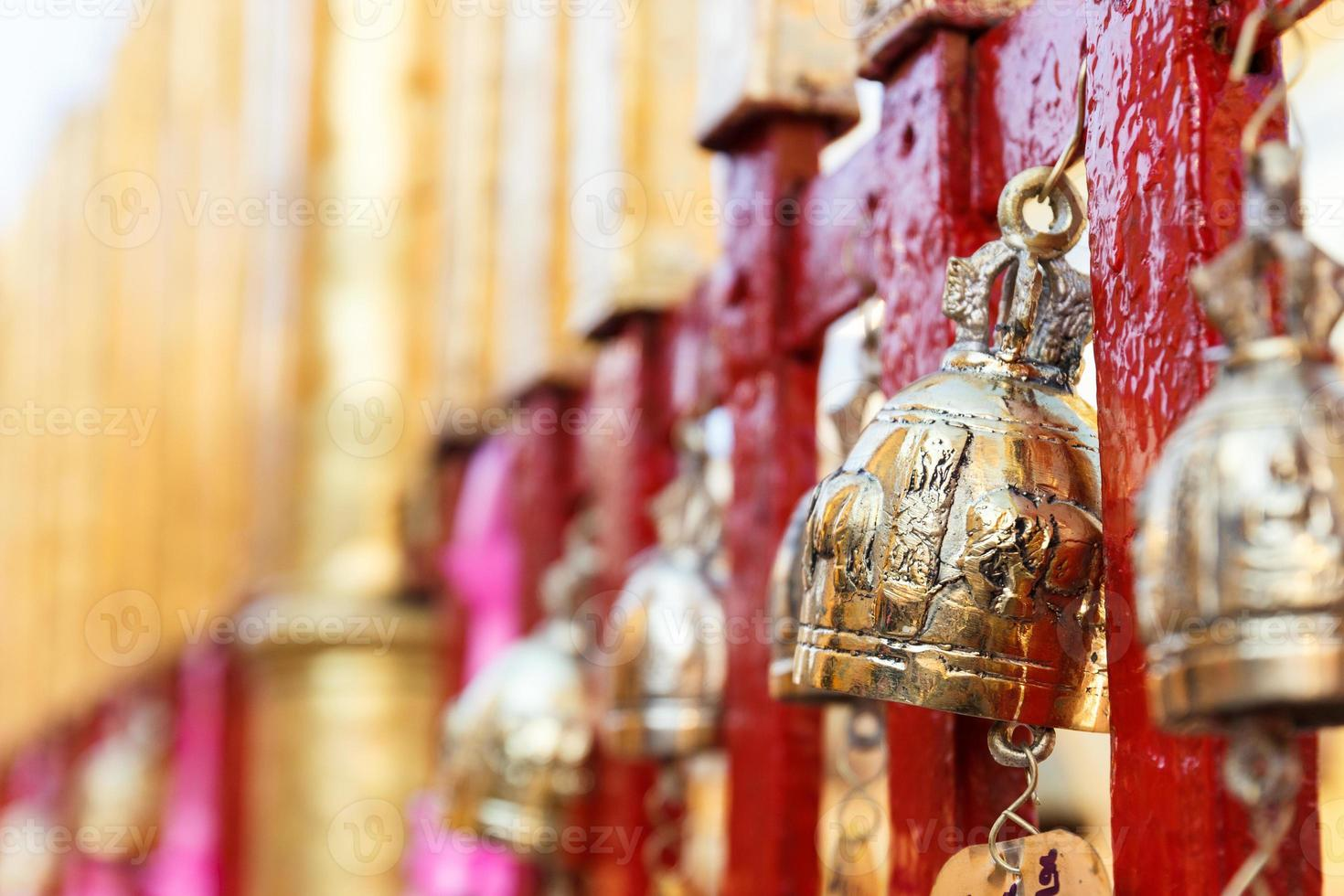 golden brass bell hanging on the temple fence photo