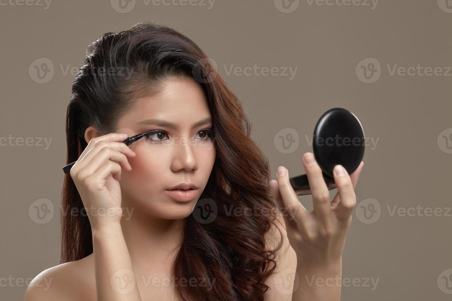 Female asian applying eye liner photo