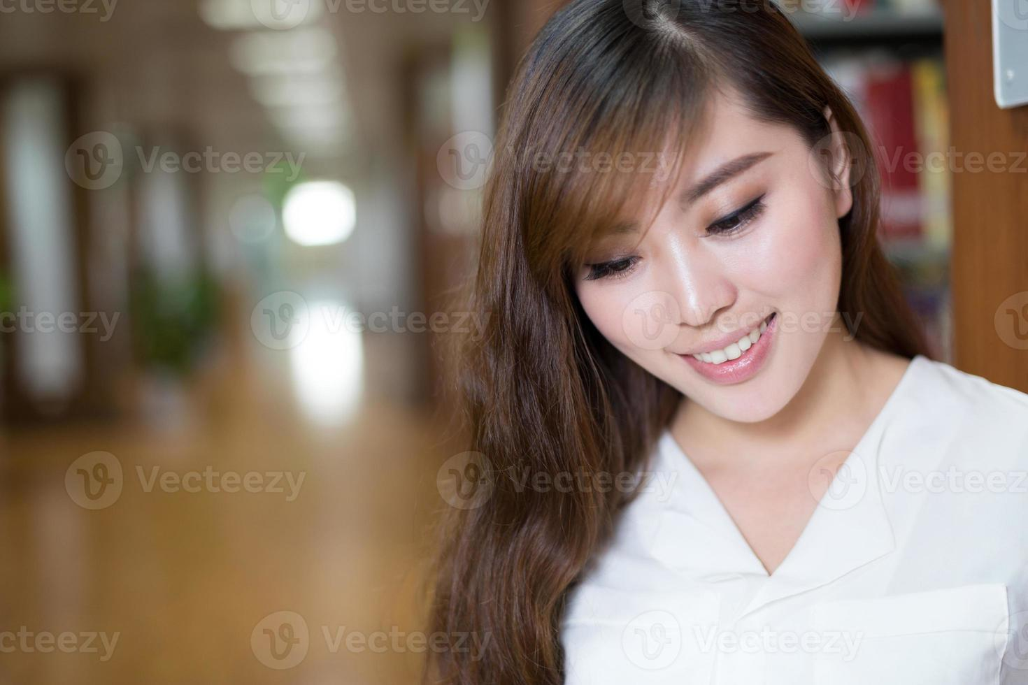 beautiful asian female student reading book in library photo