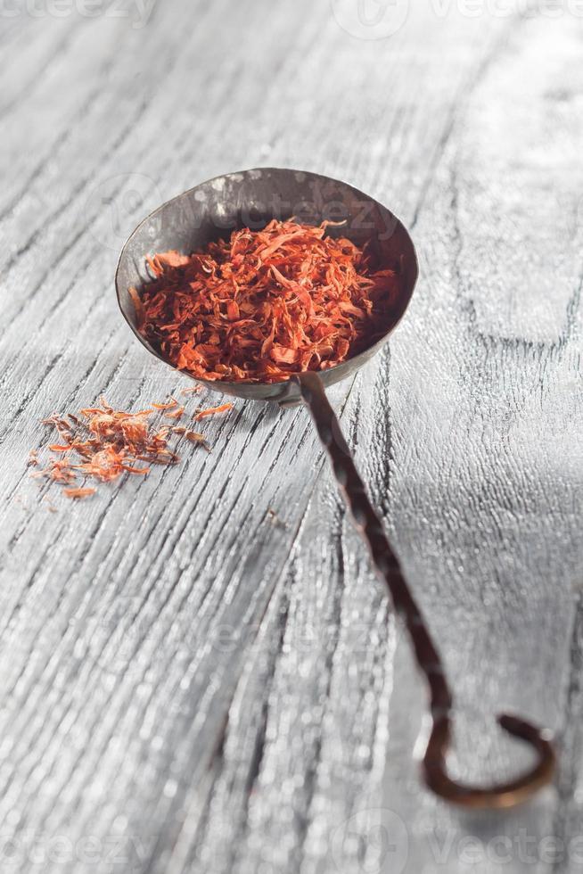 azafrán en cuchara sobre fondo de madera foto