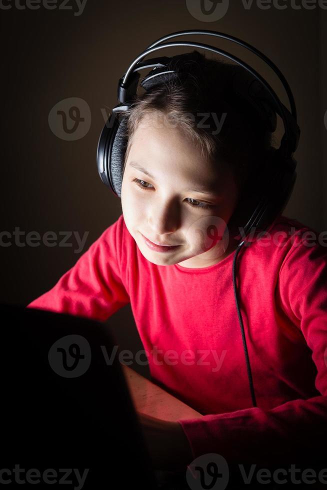 Girl with headphones using laptom in dark room listening music photo