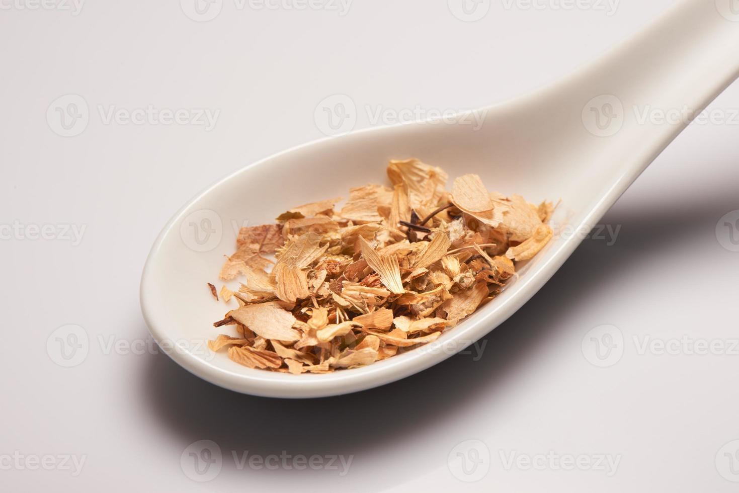 Heap of dry medical herbal tea in white ceramic spoon photo