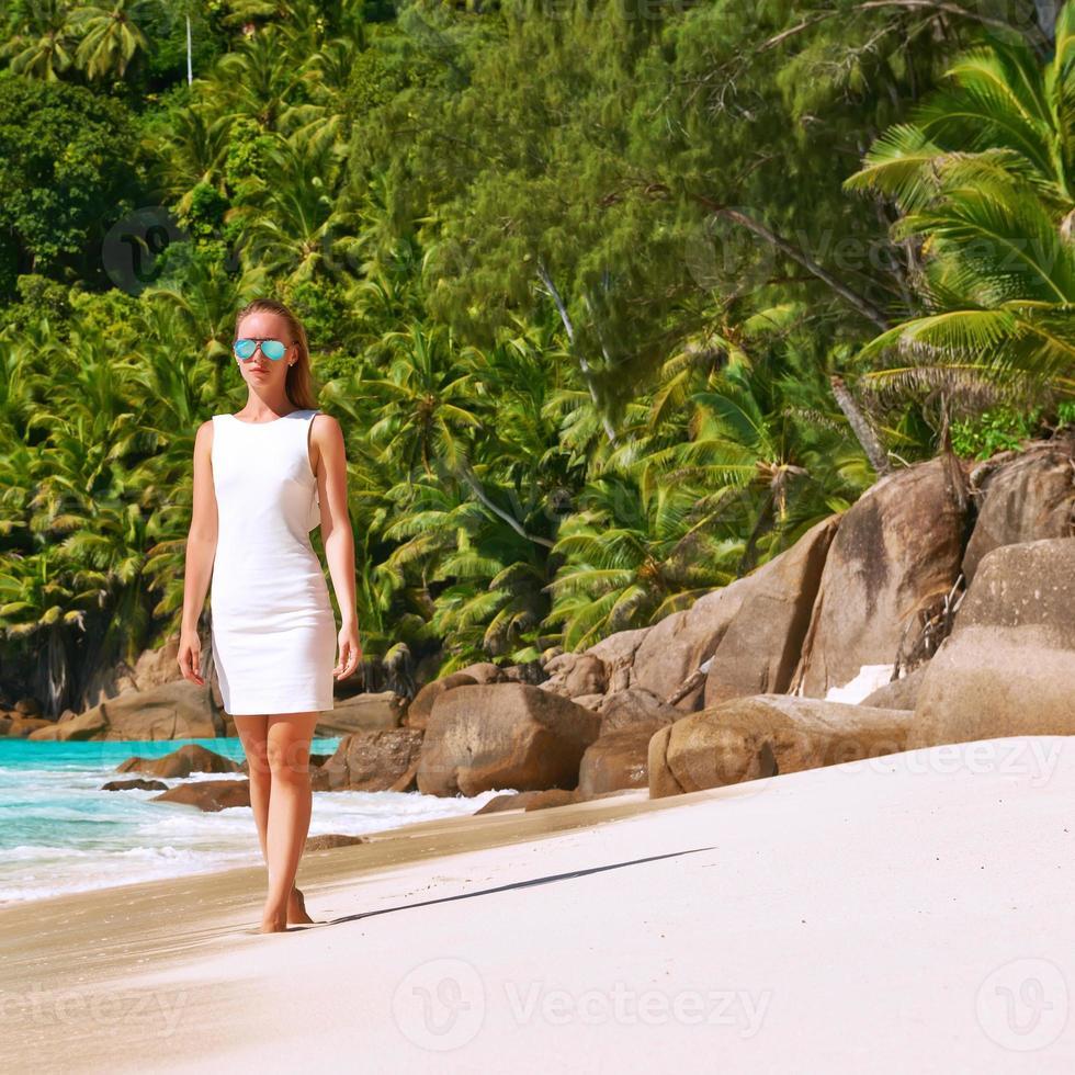 mujer con vestido en la playa en seychelles foto
