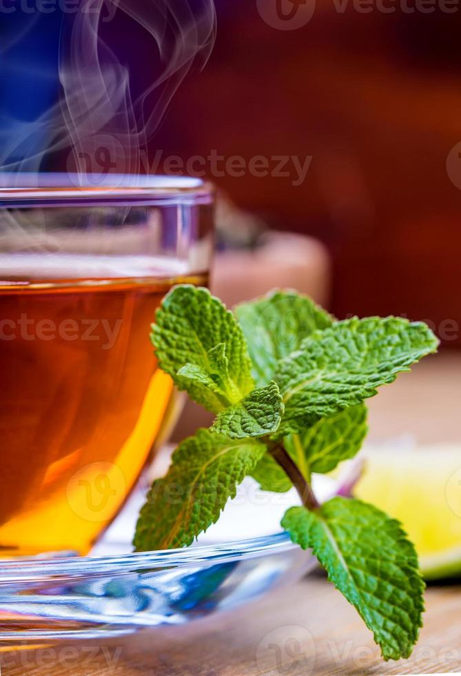 Tea in a glass cup, mint leaves photo