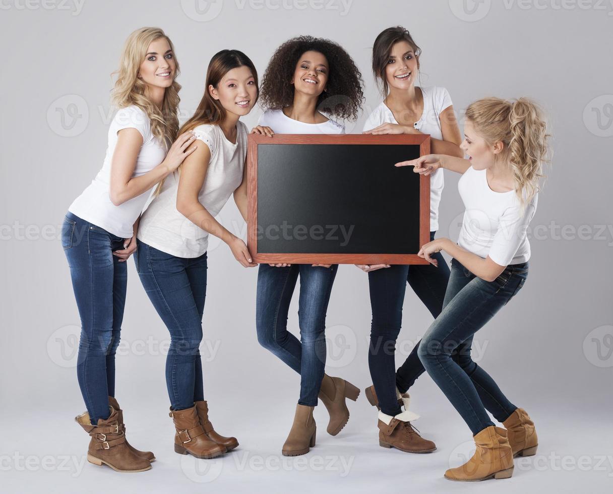 hermosas chicas sosteniendo pizarra vacía foto