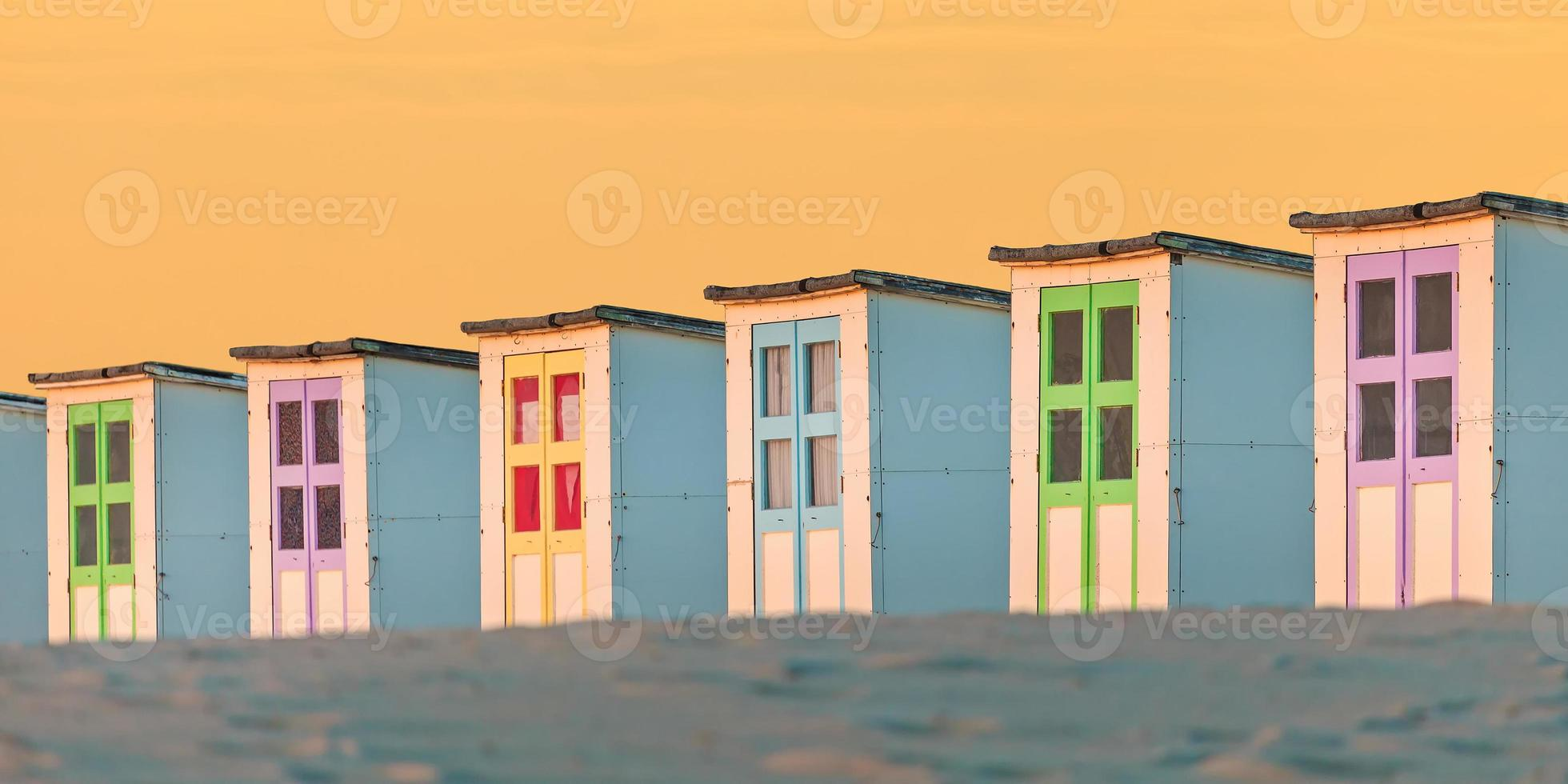 Row of old wooden beach cabins during sunset photo