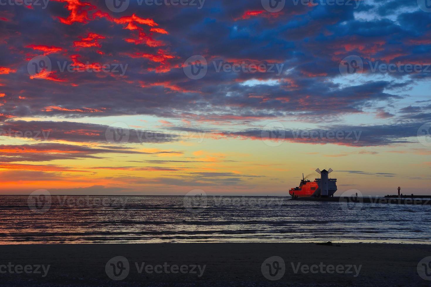 puesta de sol sobre el mar con faro foto