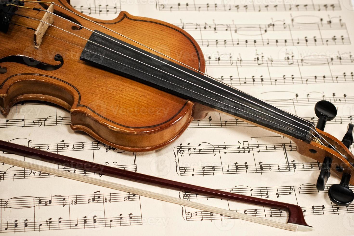 oude viool en strijkstok op muzieknoten foto
