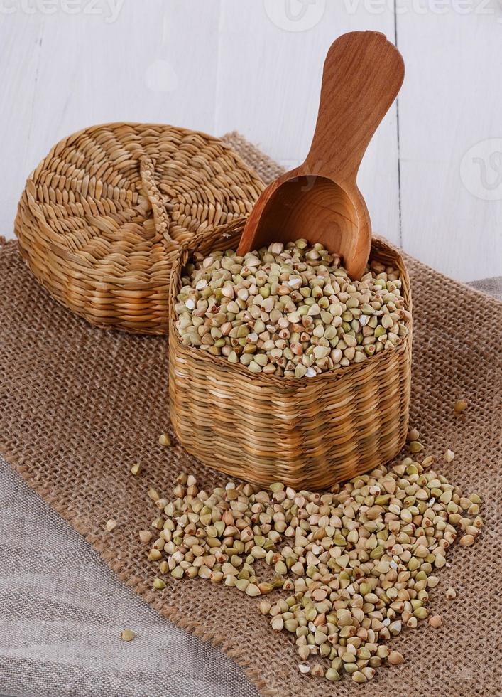 trigo sarraceno crudo en una cesta de paja sobre fondo de madera foto