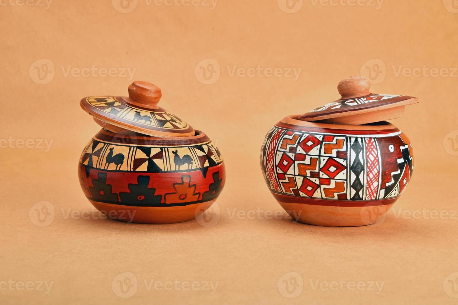 Two painted handmade ceramic pot with lids on kraft paper photo