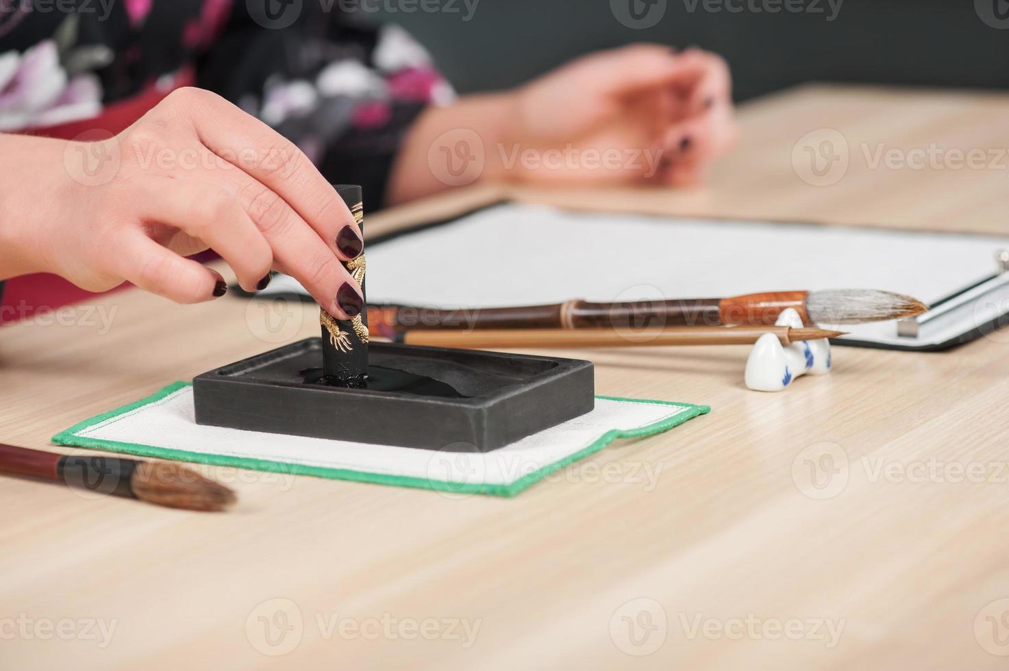 caligrafia tradicional na mesa de madeira foto
