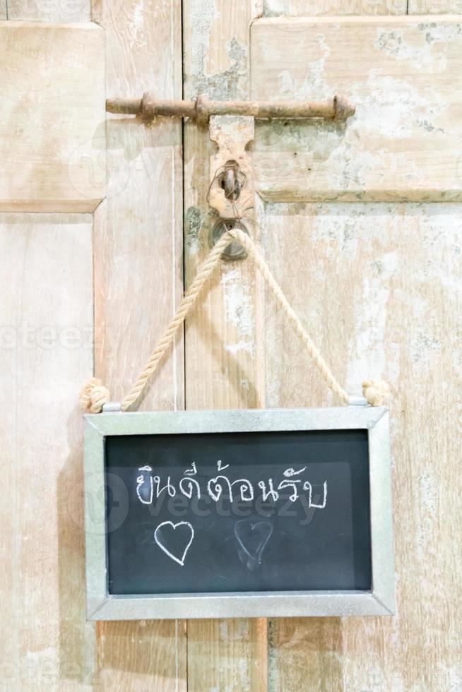 tablero de mensajes de bienvenida tailandés en la puerta de madera foto