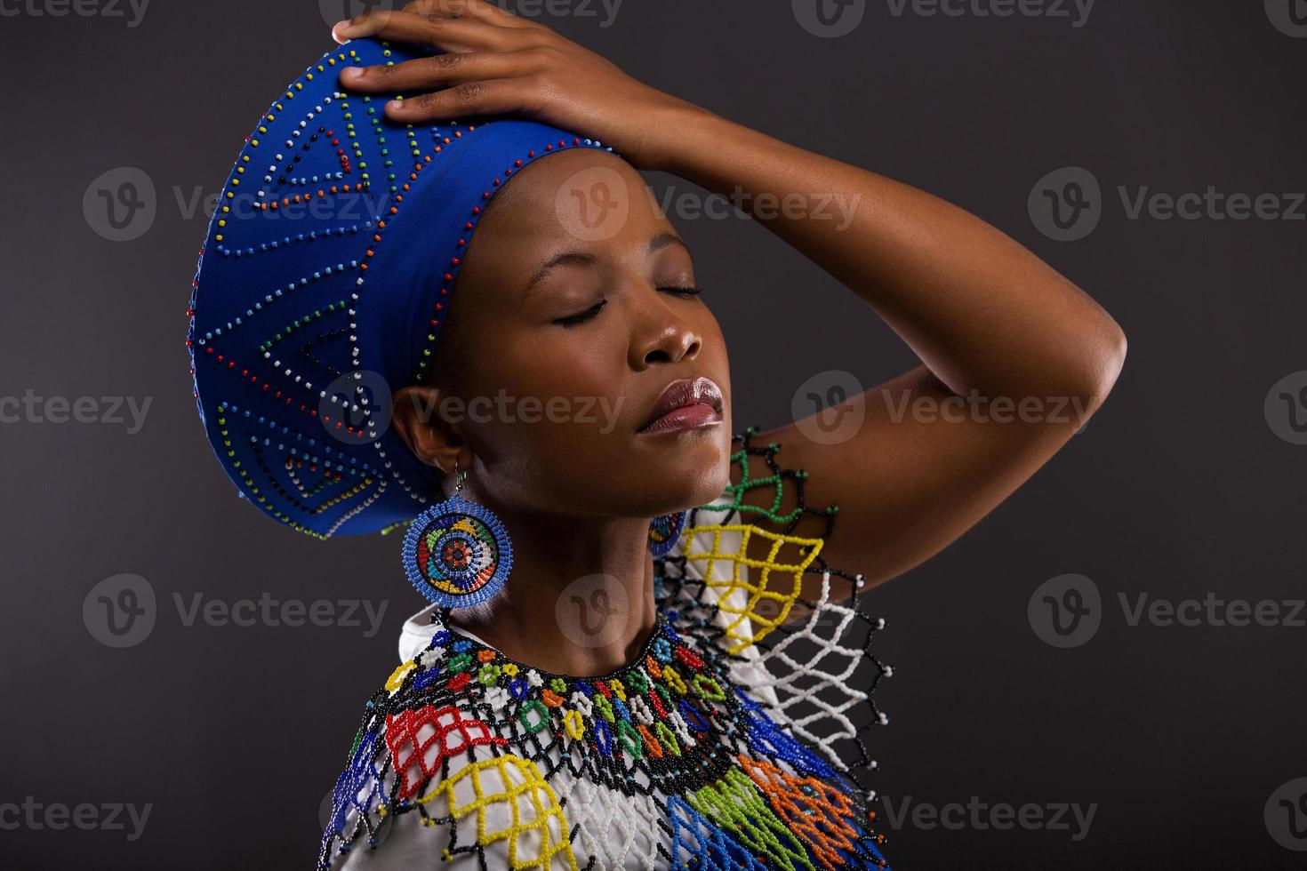 african woman in traditional clothes with eyes closed photo