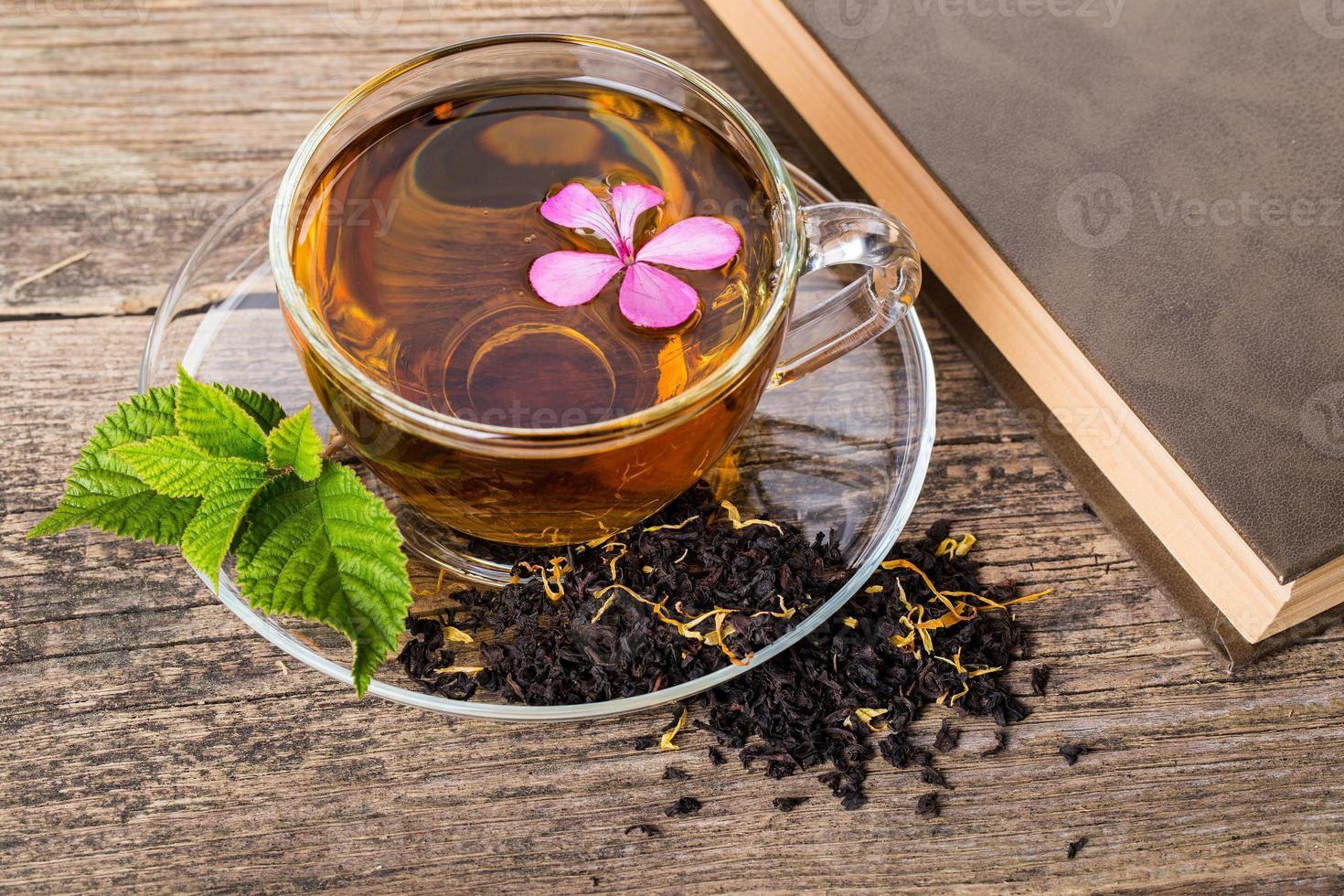 Té con flor rosa y hoja de menta, sobre madera foto