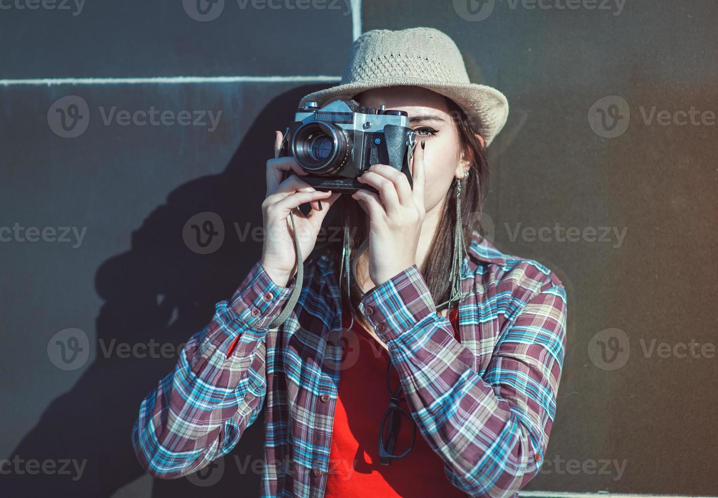 Hermosa chica hipster con sombrero haciendo foto con cámara retro