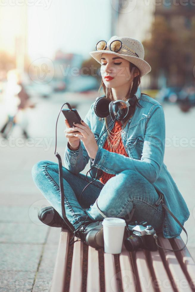 menina hippie de chapéu e óculos, ouvindo música foto