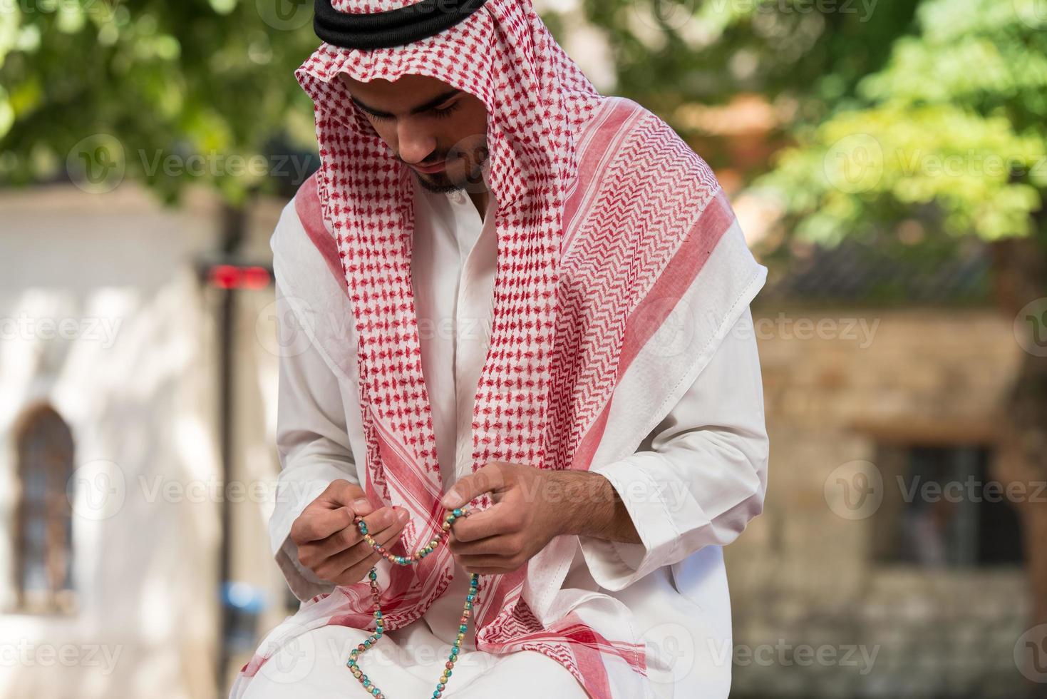 Close-up de manos masculinas rezando con Rosario foto
