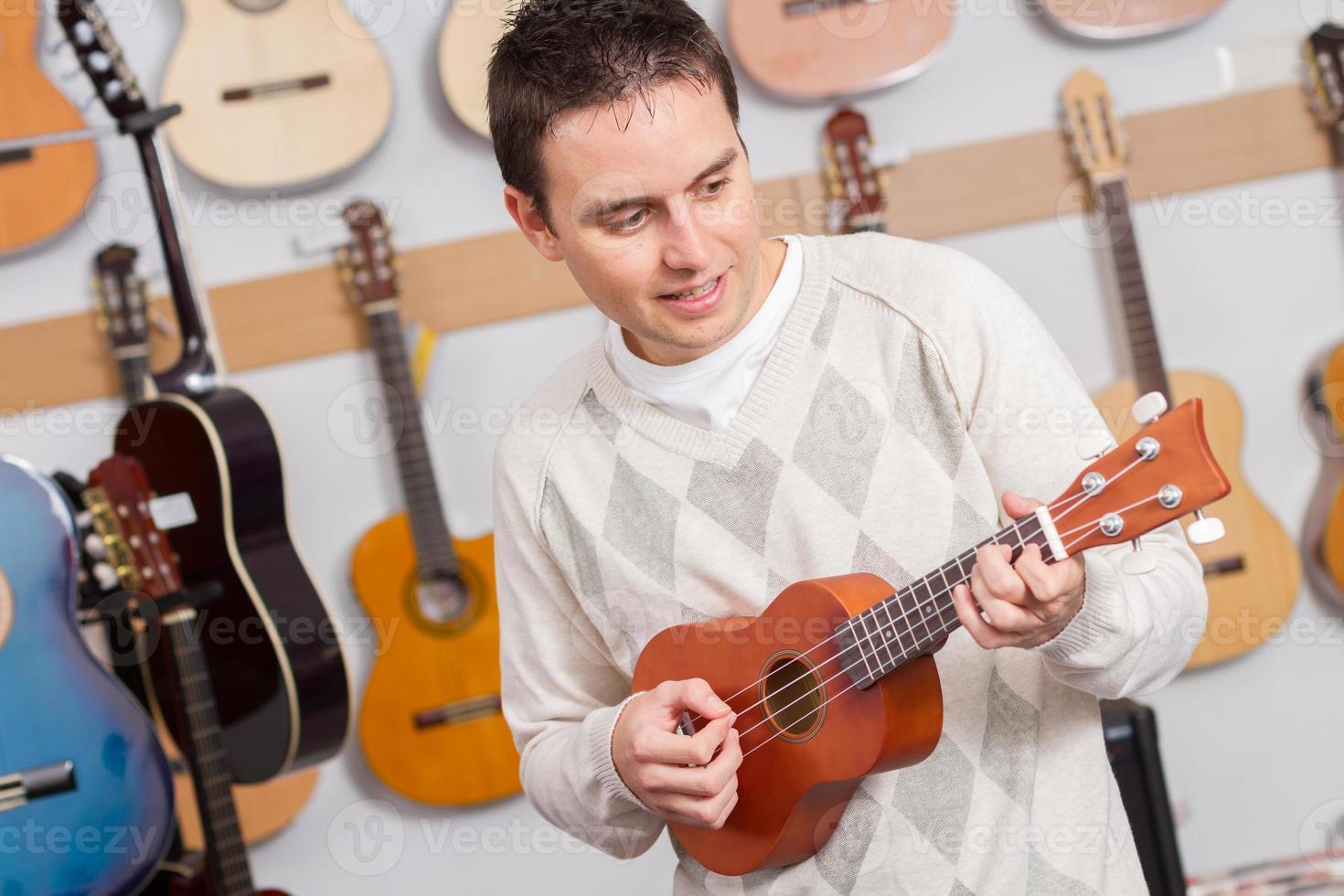 Hombre tocando ukelele en la tienda de música foto