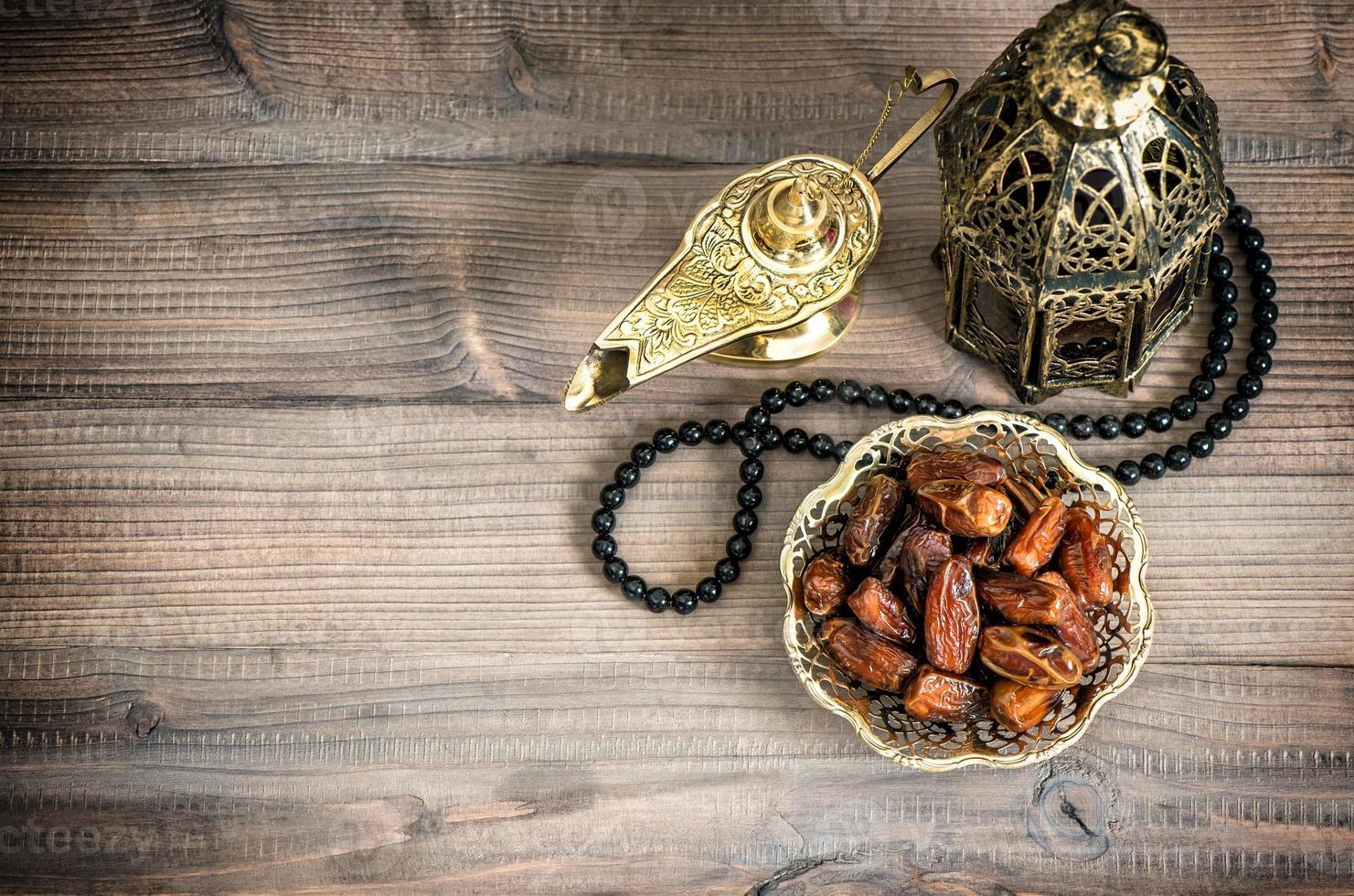 lámpara de Ramadán, rosario y fechas sobre fondo de madera foto