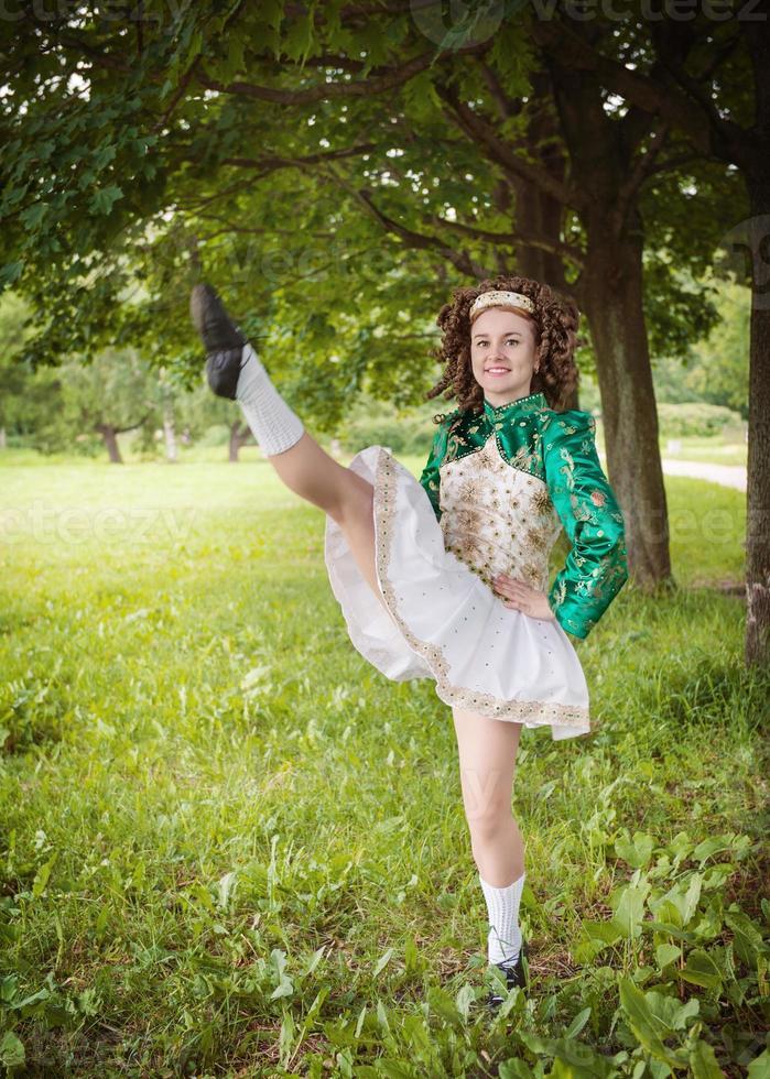 jovem menina bonita no vestido de dança irlandesa dançando ao ar livre foto