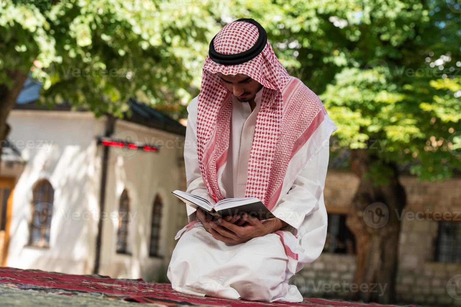 Muslim Man In Dishdasha Is Reading The Quran photo