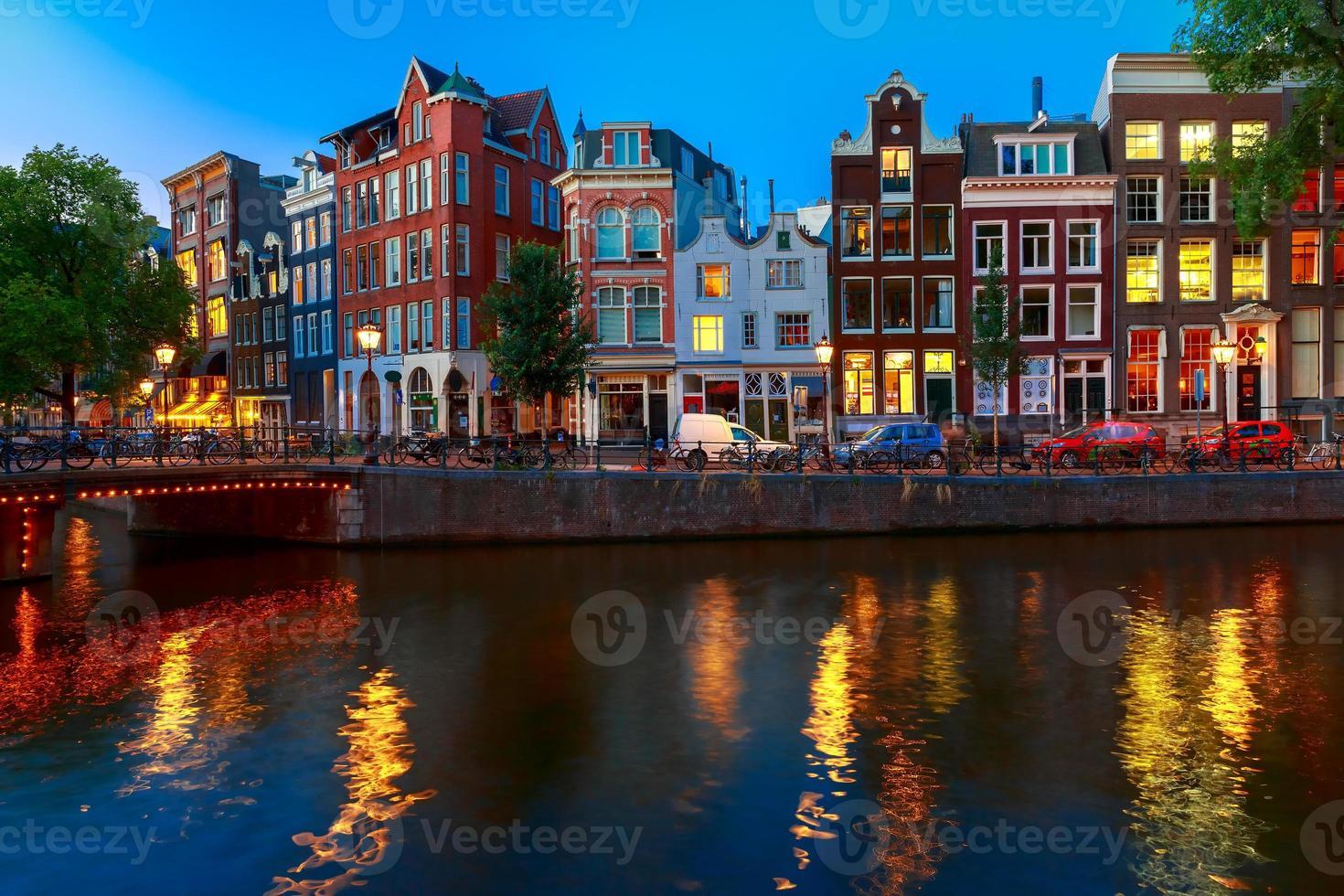 vista nocturna de la ciudad del canal de amsterdam con casas holandesas foto
